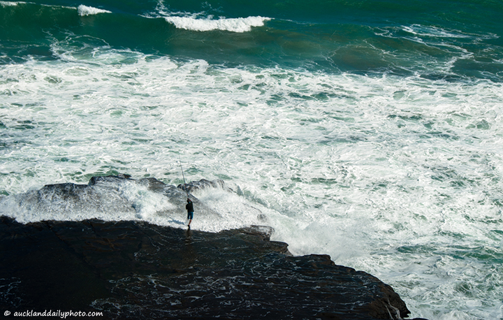Muriwai rocks fisherman
